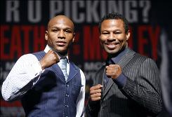 "Floyd Mayweather Jr., left, and Shane Mosley pose for photos during a news conference Wednesday in Las Vegas. The two boxers are scheduled to fight Saturday for Mosley's WBA welterweight title. ""I'm the face of boxing,"" says Mayweather, who is 40-0."