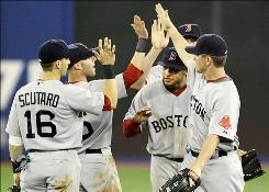 Boston's Darnell McDonald, second from right, ducks under teammates' high-fives while celebrating the the 2-0 win over Toronto.