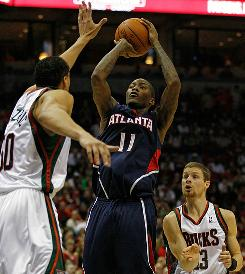 Atlanta's Jamal Crawford shoots over Milwaukee's Dan Gadzuric as Luke Ridnour watches during Game 6. Crawford, the NBA's sixth man of the year, came off the bench to score 24 points as the Hawks won to send the series back to Atlanta for Game 7.