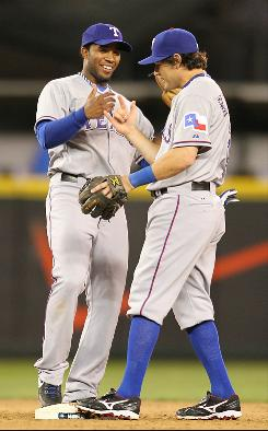 The Rangers' Ian Kinsler, right, and Elvis Andrus celebrate after defeating the Seattle Mariners 2-0 in 12 innings. Andrus scored the winning run on a wild pitch.