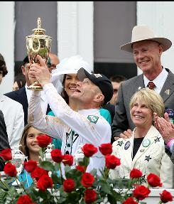 Jockey Calvin Borel holds the 136th Kentucky Derby trophy in the winners circle as Super Saver's owner owner Bill Casner, right, looks on. The jockey's victory gave trainer Todd Pletcher his first Kentucky Derby victory after 24 failures.