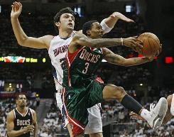 Bucks guard Brandon Jennings tries to drive around Hawks defender Zaza Pachulia during the second quarter of Game 7.