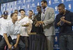 LeBron James receives the NBA MVP trophy as he shares the stage with Cavaliers teammates on the University of Akron campus.