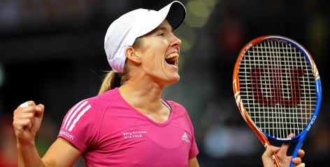 Justine Henin of Belgium celebrates her clay-court victory Sunday in Stuttgart, Germany, her first title in her comeback.