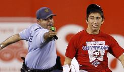 A law enforcement officer chases down a fan that ran onto the field before the eighth inning of a baseball game between the Philadelphia Phillies and the St. Louis Cardinals.