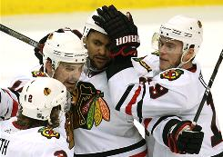 Dustin Byfuglien, center, scored a hat trick to help the Blackhawks beat the Canucks in Game 3.