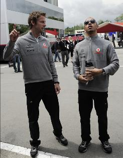 Britain's Jenson Button, left, and teammate and compatriot Lewis Hamilton talk in the paddock at the track in Montmelo, just outside Barcelona, ahead of Sunday's Spanish Grand Prix.