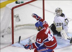 Penguins goaltender Marc-Andre Fleury looks on as the Canadiens' Roman Hamrlik celebrates teammate Brian Gionta's goal during the third period of Game 4 Thursday night in Montreal.