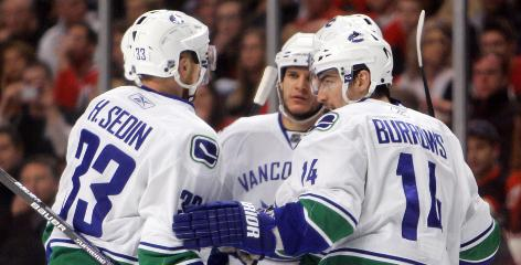 Vancouver Canucks defenseman Kevin Bieksa, center, celebrates the first of his two goals Sunday night in Chicago.