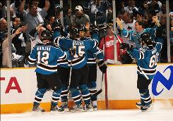 The Sharks celebrate with teammate Joe Thornton, second left, after he scored a second-period goal that helped propel San Jose into the Western Conference finals.