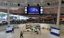 """Fans walk the """"Glory Road"""" display during opening day of the NASCAR Hall of Fame in Charlotte."""
