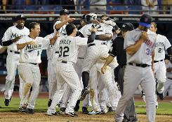 The Marlins celebrate the game-winning run as Mets reliever Fernando Nieve walks off the field.
