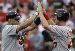 The Cardinals' Albert Pujols, left, is congratulated by Ryan Ludwick after Pujols hit a two-run home run off Reds starter Aaron Harang in the third inning.