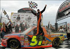 Aric Almirola celebrates his first NASCAR Camping World Truck Series win in Victory Lane after winning the Dover 200 at Dover International Speedway.