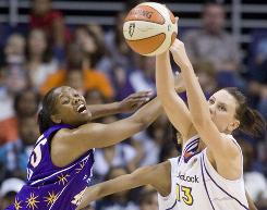 The Sparks' Noelle Quinn, left, battles for a loose ball with the Mercury's Penny Taylor during the second quarter. Taylor's free throws with 1.5 seconds remaining proved the difference in the teams' WNBA season opener.