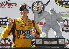 Kyle Busch, posing in victory lane with the trophy, became the second driver to win the Sprint Cup and Nationwide races in the same weekend at Dover. Harry Gant did it in September 1991.