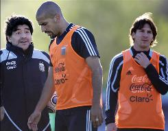 Argentina coach Diego Maradona, left, speaks to Juan Sebastian Veron as Lionel Messi looks on during a training session in Buenos Aires last fall. Messi, often compared to Maradona, will try to lead his country to World Cup glory this summer.