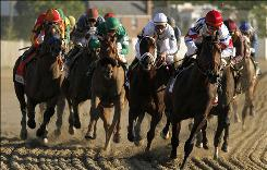 Lookin At Lucky, left, with Martin Garcia aboard, begins to make his move on the outside while Calvin Borel (white helmet), riding Super Saver, holds pace as Ramon Dominguez and First Dude, front right, maintain the lead in the third turn during Saturday's Preakness.