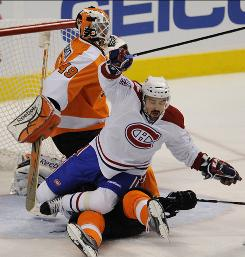 Flyers goalie Michael Leighton stays focused while Canadiens center Tomas Plekanec and Philadelphia defenseman Braydon Coburn collide in his crease.
