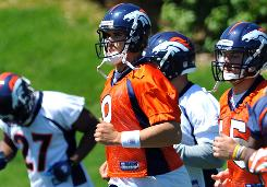Broncos QB Brady Quinn runs during the first day of the team's OTAs on May 17.