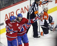 The Canadiens' Tom Pyatt, left, celebrates his goal with teammate Maxim Lapierre as Montreal won its first game of the series against Darroll Powe and the Flyers.