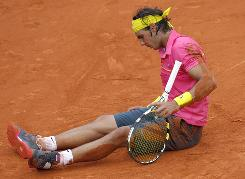Rafael Nadal takes a seat on the clay during his surprising fourth-round loss to Robin Soderling during the 2009 French Open. It was his first loss at Roland Garros.
