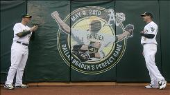 Athletics catcher Landon Powell, left, and pitcher Dallas Braden are shown near a logo commemorating Braden's perfect game against the Tampa Bay Rays before Friday's home game against the San Francisco Giants.