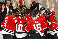 The Blackhawks surround teammate Dustin Byfuglien, third from left, after he scored the game-winning goal in overtime to give Chicago a 3-0 series lead on the Sharks.