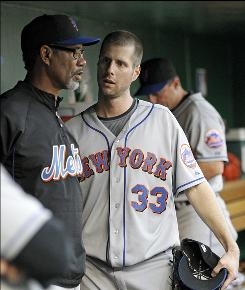 Mets pitcher John Maine talks with manger Jerry Manuel after being removed during the first inning of Thursday's baseball game against the Washington Nationals.