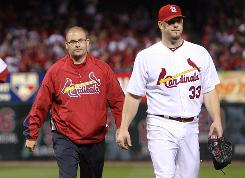 Cardinals pitcher Brad Penny is escorted off the field by a team trainer after straining his back Friday night during his start against the Los Angeles Angels. On Saturday, St. Louis put Penny on the 15-day disabled list.