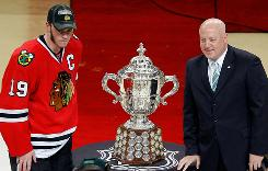 Jonathan Toews keeps his distance as he poses with deputy commissioner Bill Daly and the Clarence Campbell Trophy.