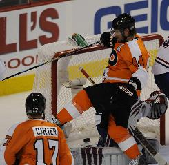 Flyers center Jeff Carter (17) scores a second-period goal as teammate Kimmo Timonen crashes into Canadiens goalie Jaroslav Halak. Carter added an empty-netter late in the third period.