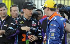 Denny Hamlin, left, talks things over with teammate Kyle Busch under much calmer circumstances, during Thursday's qualifying for the Coca-Cola 600 at Charlotte Motor Speedway.