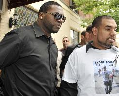 Boston Red Sox slugger David Ortiz, left, is escorted out of the wake for former major league pitcher Jose Lima at the Coppola-Migliore Funeral Home in Corona, N.Y.