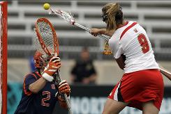Maryland's Laura Merrifield (9) scores over Syracuse goalie Liz Hogan during the first half of their NCAA tournament semifinal. Maryland won 14-5 to secure a spot in the national championship game.