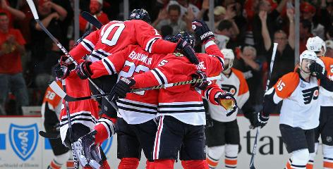 Patrick Sharp (10) leaps into the pile of players celebrating Troy Brouwer's goal. The line of Sharp, Brouwer and Marian Hossa combined for three goals and three assists.
