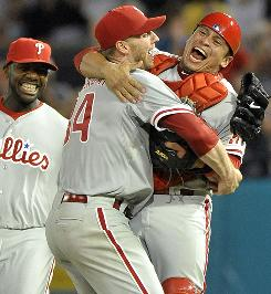 Phillies ace Roy Halladay celebrates the second perfect game in franchise history with catcher Carlos Ruiz and Ryan Howard.