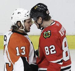 Philadelphia Flyers left wing Daniel Carcillo and Chicago Blackhawks right wing Tomas Kopecky confront each other after a hit in the first period of Game 2 .