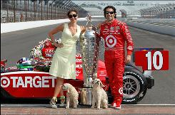 Dario Franchitti poses with his wife, actress Ashley Judd, their dogs, Buttermilk and Shug, and the Indy 500 trophy Monday on the famed bricks of Indianapolis Motor Speedway.
