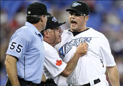 Blue Jays closer Kevin Gregg, right, is ejected in the 9th inning by home plate umpire Angel Hernandez as bench coach Nick Leyva restrains him. The Rays scored four runs in the top of the ninth off Gregg.