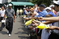 Tiger Woods walks past fans Wednesday on his way to the practice range at the Memorial at Muirfield Village Golf Club in Dublin, Ohio.