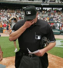 Jim Joyce wipes away tears during the lineup card exchange with Armando Galarraga, the pitcher who lost a perfect game on the umpire's admitted blown call.