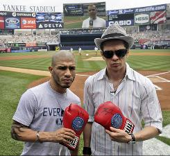 Boxers Miguel Cotto, left, and Yuri Foreman pose for a picture before the New York Yankees baseball game against the Baltimore Orioles on Thursday. Foreman will defend his WBA light middleweight title against Cotto on Saturday, the first bout in Yankee Stadium in 34 years.