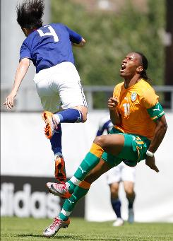 Ivory Coast forward Didier Drogba, right, winces after a challenge from Japan's Marcus Tulio Tanaka during an international exhibition in Switzerland.