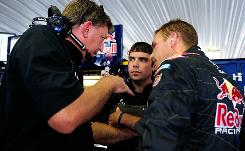 Scott Speed, right, talks with crew chief Ryan Pemberton, left, and another crewmember during practice at Pocono Raceway.