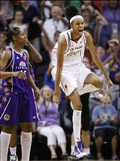 The Mercury's DeWanna Bonner reacts in front of the Sparks' Noelle Quinn after assisting on her team's game-winning shot in Phoenix.