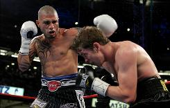 Miguel Cotto delivers a left to the face of Yuri Foreman during their title fight at Yankee Stadium.
