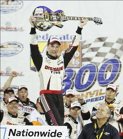 Brad Keselowski raises the custom Gibson guitar trophy after winning the Federated Auto Parts 300 at Nashville Superspeedway.