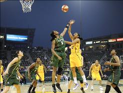 Los Angeles Sparks Forward Tina Thompson, right, shoots over Seattle Storm forward Swin Cash during in the first half of their game at The Home Depot Center Tennis Stadium in Carson, Calif.