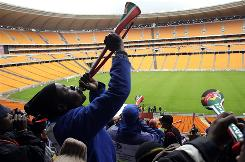 Construction workers blow vuvuzelas, noisemakers favored by South African soccer fans, last month at Soccer City stadium in Johannesburg, site of Friday's World Cup opener against Mexico.